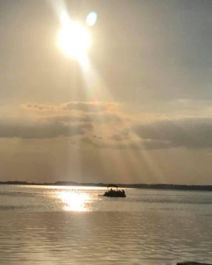 sunset of lake eustis as a rental boat sails off